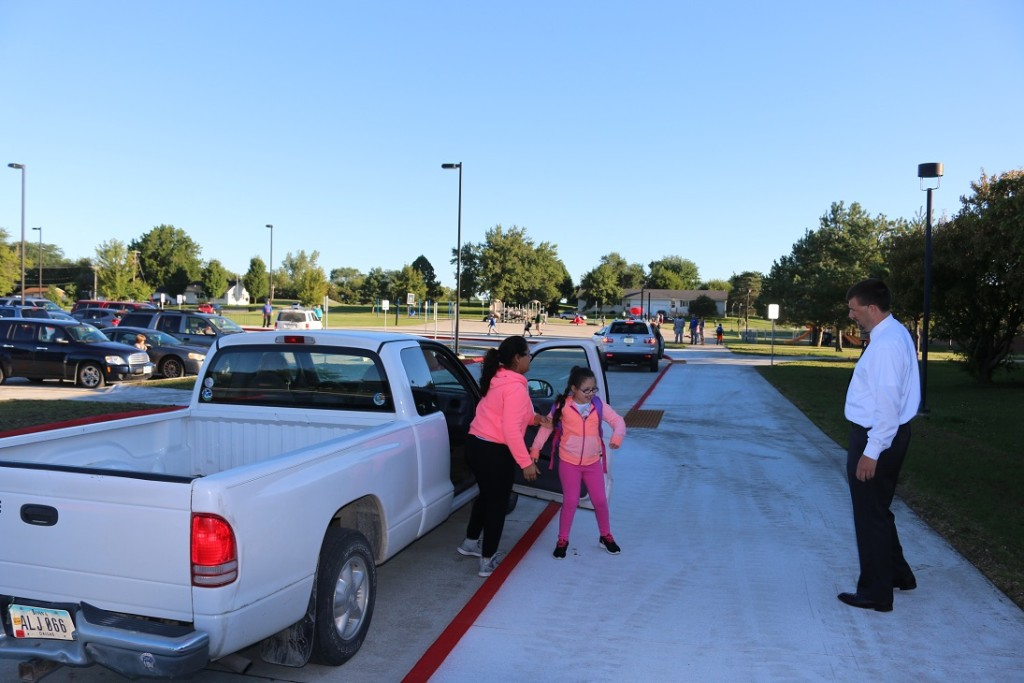 Perry Elementary School Principal Trevor Miller, right, helped direct students and parents in the new parking lot and drive-through routes.