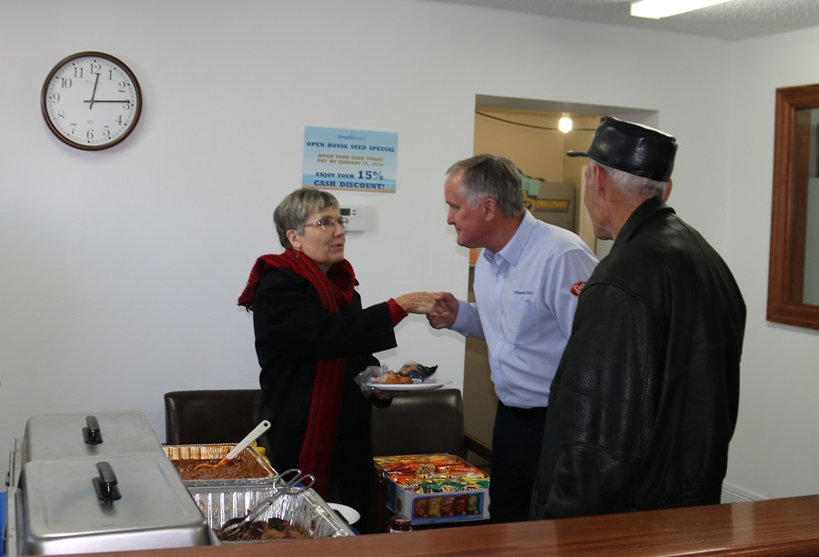 Rodger Reinhart, center, Simplex Seed director of sales and marketing, greeted visitors to the open house, which included pulled pork sandwiches catered by Hy-Vee.