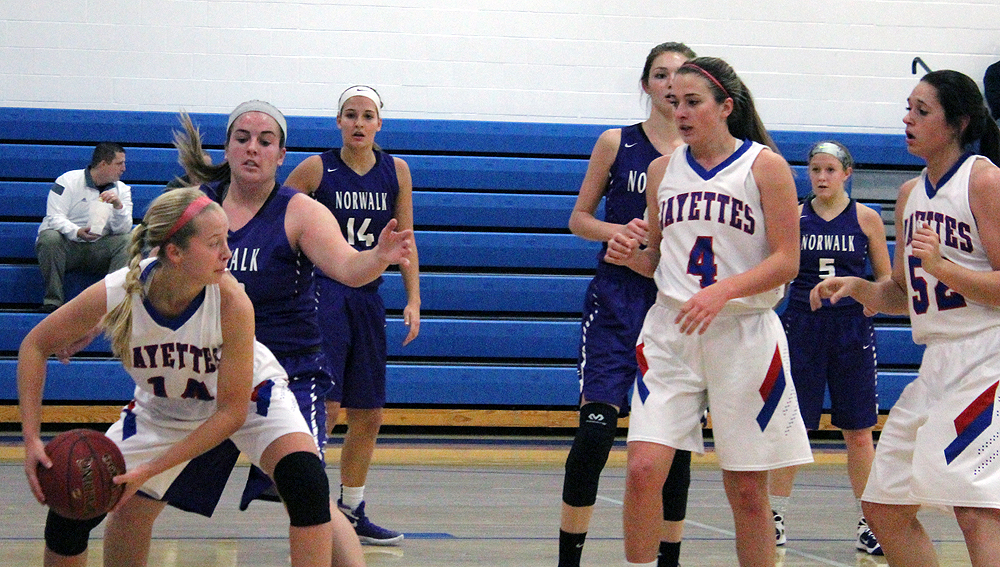Emma Olejniczak pulls down an offensive rebound as teammates Victoria Hegstrom (4) and Taylor Lathrum (52) look on.