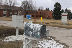 Delicate and protracted negotiations between county, state and federal authorities resulted in the erection of a cluster box unit (CUB) to replace the simple old mailbox at the former site of the county poor farm, now rebranded the Dallas County Human Services Campus. Who actually fetches the mail from the CBU is governed by contract terms negotiated between the state of Iowa and UE Local 893, the Iowa United Professionals union.