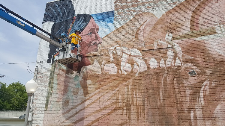 Woodward muralist Dennis Adams said he is working from west to east on the wall-sized mural.