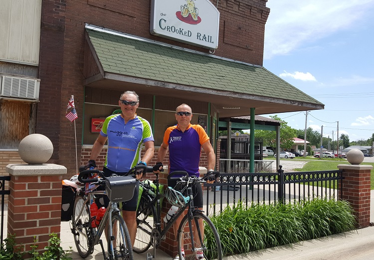 Chris Watson, left, and David Knight prepare to remount and resume their transcontinental bike ride, seemingly grateful for their encounter with a bit of local color in Perry, Iowa.