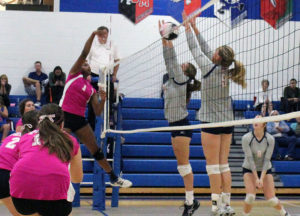 Perry's Jo Diw powers one of her 14 kills against Ballard Tuesday as teammates Sid Vancil (2) and Adrian Thompson watch.